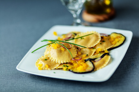 Vegetarian Italian ravioli pasta with grilled or roasted slices of eggplant or aubergine served on a modern square plate topped with fresh chives