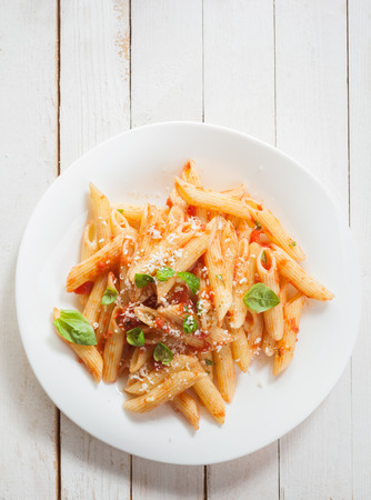 Overhead view of a healthy plate of Italian penne pasta with basil, savory spicy sauce and grated parmesan cheese on rustic white wooden boards with copyspace