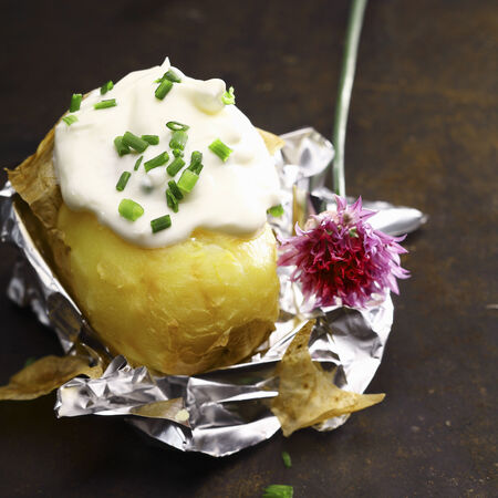 Foil baked potato with sour cream and chopped fresh chives with a flower off a chive plant served partially peeled on its foil wrapper