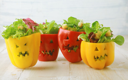 Foto de Colorful Halloween food background with colorful healthy stuffed red and yellow sweet bell peppers with cutout faces in the skin like Halloween jack-o-lanterns filled with green salad and cheese - Imagen libre de derechos