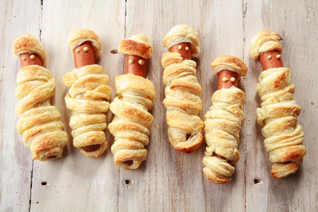 Six Weiners Wrapped in Pastry to Look Like Halloween Mummies on Wooden Background
