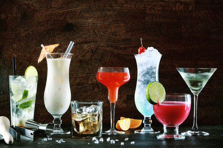 Selection of colorful festive Christmas drinks, alcoholic beverages and cocktails in elegant glasses on a dark background with copyspace