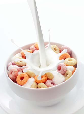 Pouring fresh creamy milk into a bowl of colorful fruit loops breakfast cereal in a white ceramic bowl with a splash on a white background with copyspace