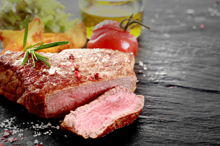 Healthy trimmed lean medallion of grilled rare rump steak sliced through to show the texture seasoned with salt and herbs on an old wooden surface with ingredients and copyspace