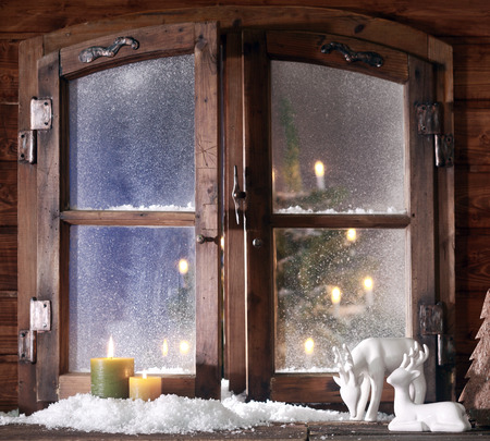 Christmas Items - Snow Formed Reindeer and Colored Lighted Candles at Wooden Window Pane with Glowing Christmas Tree at the Back.