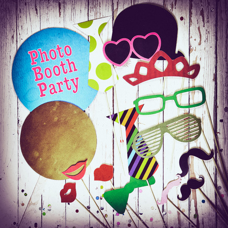 Fun photo booth party background with colorful paper fashion accessories, lips, moustaches and balloons with text - Photo Booth Party - surrounded by a vignette, square format