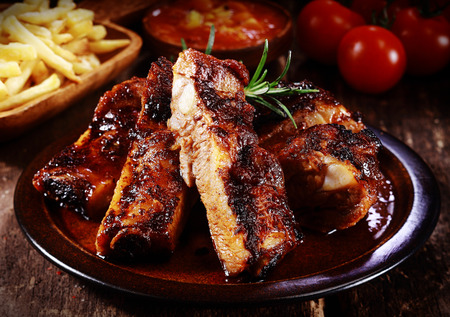 Foto de Plate of delicious spicy marinated grilled or barbecued spare ribs served with French Fries and tomato at a steakhouse or restaurant, close up view - Imagen libre de derechos