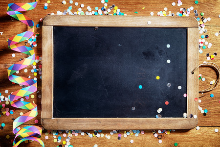 Photo pour Close up Empty Black Board on Wooden Table with Colorful Streamers and Confetti. Emphasizing Copy Space. - image libre de droit