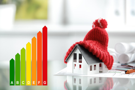 Foto de Energy efficiency concept with energy rating chart and a house with red bobble hat - Imagen libre de derechos