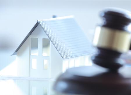 Foto de Close up Conceptual White Miniature House on Top of the Table Beside Court Gavel. - Imagen libre de derechos