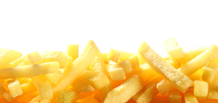 Border showing the close up texture of a pile of French fries or fried potato chips over white with copyspace for a restaurant, tuck shop or cafeteria