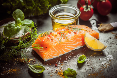 Photo for Preparing a gourmet salmon meal with a thick succulent fish fillet, olive oil, herbs, spice rub and seasoning on a kitchen counter, close up view - Royalty Free Image