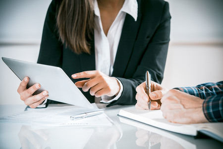 Photo pour Two business people in a meeting discussing information on a tablet-pc and taking notes as they work together as a team, close up view of their hands seated at a desk - image libre de droit