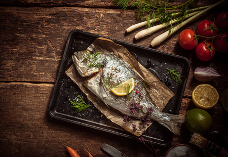 Foto de Fish Meat on a Black Tray with Herbs and Spices on Top of a Rustic Wooden Table with Organic Veggies. Captured in High Angle View. - Imagen libre de derechos