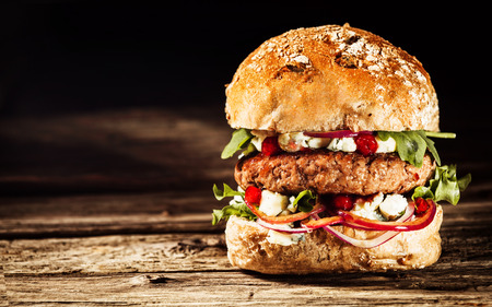 Foto de Close Up of Burger Piled High with Fresh Toppings on Whole Grain Artisan Bun, on Rustic Wooden Surface with Dark Background and Copy Space - Imagen libre de derechos