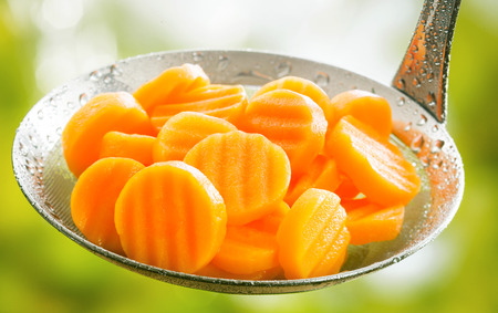 Healthy boiled or steamed crinkle cut sliced farm fresh carrots in a kitchen ladle ready to be served as an accompaniment to a meal