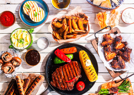 High Angle View of Grilled Meal - Appetizing Barbequed Meats and Vegetables Arranged on White Wooden Picnic Table