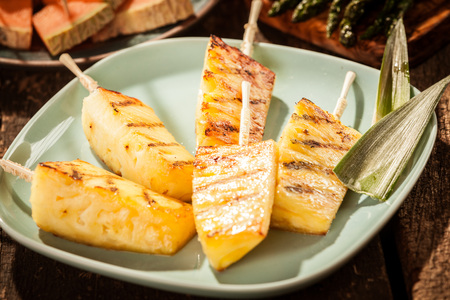 Close Up of Grilled Pineapple Wedges on Wooden Skewers on Green Plate Surrounded by Plates of Other Food on Wooden Table