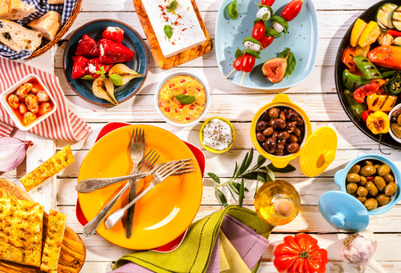 Photo pour High Angle View of Prepared Colorful Mediterranean Meal Spread Out on Painted White Wooden Picnic Table with Bright Plates and Cutlery - image libre de droit