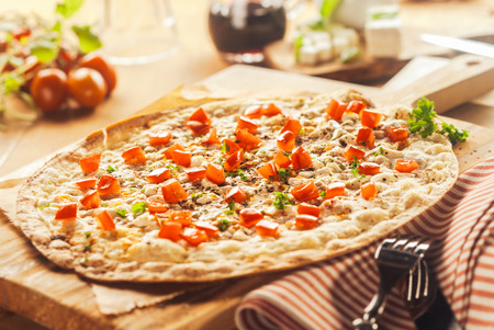 Close Up of Rustic Thin Crust Pizza on Wooden Cutting Board Surrounded by Fresh Ingredients and Cutlery