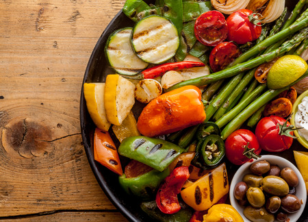 High Angle View of Bounty of Colorful Grilled Vegetables and Olives Served on Cast Iron Pan and Resting on Wooden Table Surface with Copy Spaceの写真素材