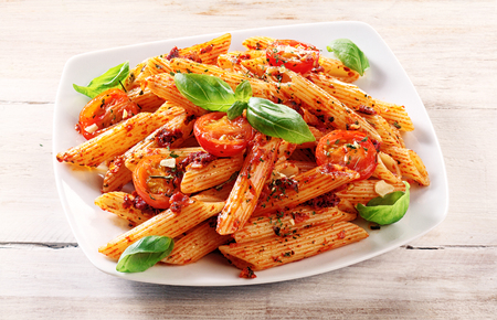 Foto de Close up Gourmet Tasty Spicy Italian Penne Pasta with Tomato and Herbs on a White Plate, Served on Top of a Wooden Table. - Imagen libre de derechos