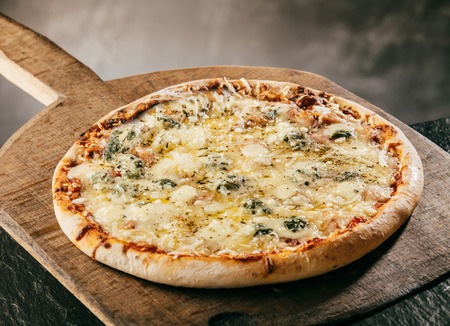 Flame grilled Italian Four Cheeses Pizza served steaming hot on a wooden board in a pizzeria or restaurant for a tasty savory fast food snack or takeaway, close up high angle view
