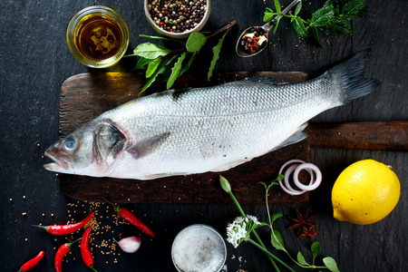 Foto de High Angle View of Fresh Raw Whole Fish on Rustic Wooden Cutting Board Surrounded by Fresh Herbs and Spices for Seasoning and Garnishing - Imagen libre de derechos