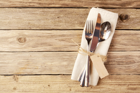 Photo for Close up Spoon, Fork and Knife Tied on White Napkin with Empty Tag, on Wooden Table with Text Space. - Royalty Free Image