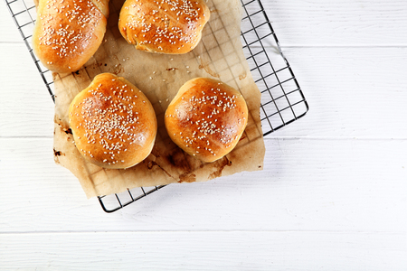 High Angle View of Homemade Fresh Burger Buns on a Wire Rack with Paper, Served on a White Wooden Table.