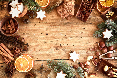 Traditional Xmas frame with spices, speculoos biscuits, star cookies and assorted nuts decorated with dried orange around central copyspace on a rustic wood background for your Christmas message