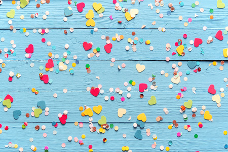 Blue wood background with scattered colorful party confetti with heart shapes in a closeup full frame overhead view for festive or celebration themed concepts