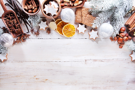 Festive seasonal Christmas border of assorted nuts, spices, orange slices, vanilla, cookies and decorations on a rustic white wood background with copyspace viewed from above