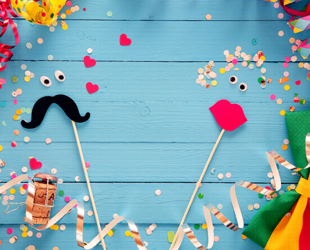 Fun photo booth accessories festive background with a loving couple formed from a mustache and set of luscious red female lips on rustic blue wooden boards with a frame of party streamers and bow tie