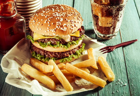 American double cheeseburger on a sesame bun served with crisp golden French fries, a soda or soft drink and ketchup as a fast food takeaway outdoors on a rustic table