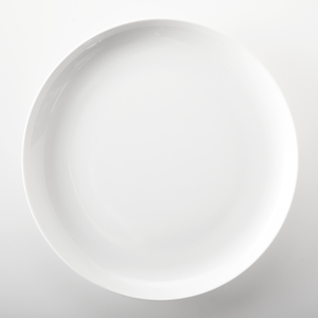 Empty plain white round generic dinner plate with place for placement of food or a recipe viewed close up overhead over a white background in square format