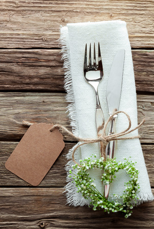 Foto de High Angle Close Up of Silver Wedding Knife and Fork Tied with String and Blank Tag on White Napkin with Fringed Edges and Heart Shaped Wreath Made from Greenery and Small White Flowers - Imagen libre de derechos