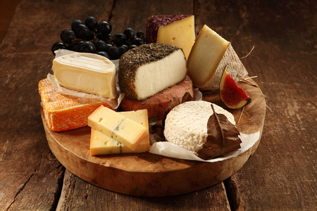 Assorted gourmet cheeses on a rustic wooden platter with soft, semi-hard, goat milk and speciality varieties served with fresh figs and grapes