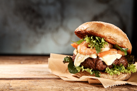 Foto de Tasty grilled prawn and beef burger with lettuce and mayonnaise served on pieces of brown paper on a rustic wooden table of counter, with copyspace - Imagen libre de derechos