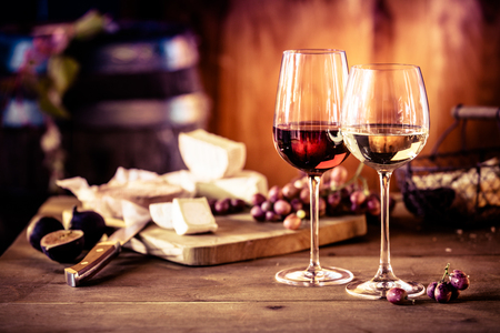 Cheese platter with fresh grapes and glasses of red and white wine on a rustic wooden table in front of a blazing fire in a tavern or winery