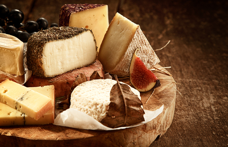 Close Up of Gourmet Cheese Tray Served on Wooden Board - Variety of Cheeses on Rustic Wood Table with Fruit Garnish and Copy Space