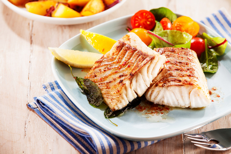 Foto de To portions of fresh grilled pollock or coalfish served with colorful salad and slices of lemon, close up high angle view - Imagen libre de derechos