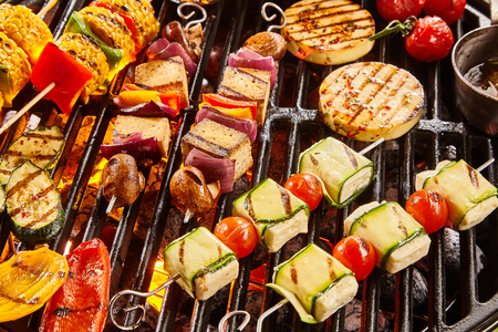 Photo pour Assorted shish vegan or vegetarian kebabs with tofu and haloumi grilling on a grill over barbecue with colorful tomatoes and bell peppers, onion and eggplant for a tasty summer picnic - image libre de droit