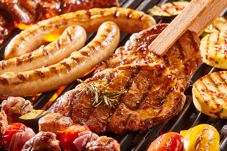 Delicious assortment of meat neck steak and vegetables grilling on a BBQ with pork sausages, chops, skewers with mixed kebabs, bell pepper and eggplant in a close up view with tongs turning a cutlet
