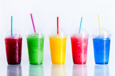 Foto de Panoramic Still Life of Colorful Frozen Fruit Slush Granita Drinks in Plastic Take-Away Cups with Lids and Drinking Straws in front of White Background - Imagen libre de derechos