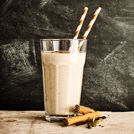 Photo for Single glass of blended cinnamon drink with two straws on a long rustic table against a black dusty chalkboard - Royalty Free Image