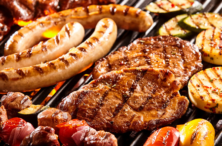 Hot dog sausages, beef steak, chicken patties and vegetables on hot flaming grill