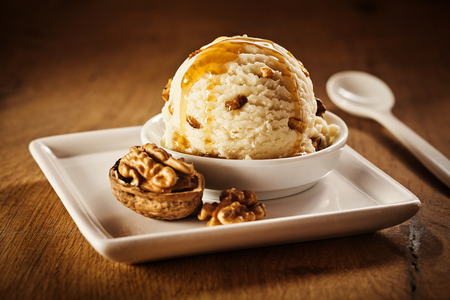 Photo for Delicious sweet vanilla ice cream dessert with coating of caramel syrup and whole cracked walnut beside it on square plate - Royalty Free Image