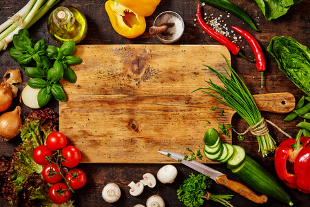High Angle Still Life View of Knife and Wooden Cutting Board Surrounded by Fresh Herbs and Assortment of Raw Vegetables on Rustic Wood Tableの写真素材