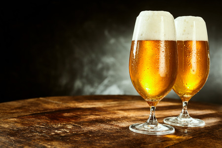 Foto de Two glasses full of beer on weathered wooden table with black and gray background - Imagen libre de derechos